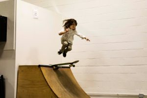 young boy skateboarding on indoor ramp